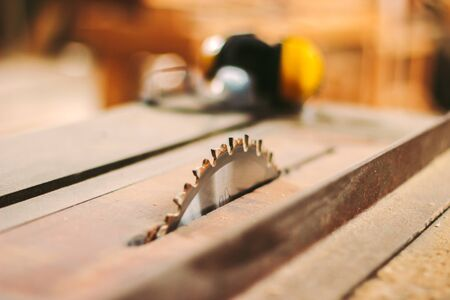 Closeup sharp steel blade of electric circular saw table at woodworking production workshop. Professional power sawing machine for cutting wooden boards, planks at sawmill factory. Carpenter workplace