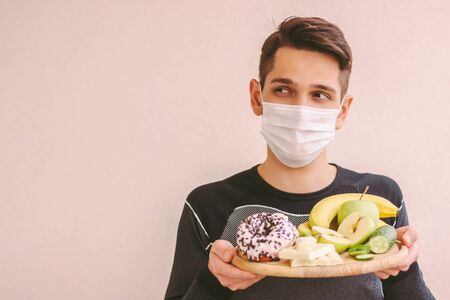 Uncertain sports man in medical face mask hold wooden board with junk and healthy food, look at copy space. Fitness man in protective mask struggling: sweets or fruits. Quarantine dieting nutrition