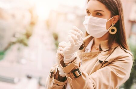 Beautiful young stylish woman in protective face mask put on medical latex gloves outdoors. Trendy elegant hipster girl in medical face mask wear protective gloves on city street. COVID-19 protection