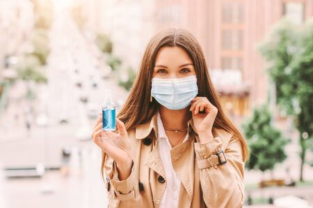 Beautiful happy woman in protective mask hold antibacterial gel bottle in hand outdoors. Stylish hipster girl in medical face mask with sanitizer dispenser on city street. Hygiene, safety, COVID-19 免版税图像