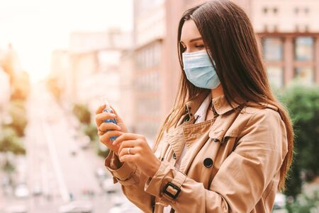Beautiful young hipster woman in medical face mask apply antiseptic gel on palm on city street. Happy stylish girl in protective mask using antibacterial sanitizer on hand outdoors. Personal hygiene