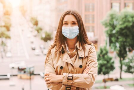 Young beautiful elegant woman in medical face mask keep arms crossed on city street. Stylish happy hipster girl in protective face mask outdoors. COVID-19 coronavirus personal protection, travel Stock fotó