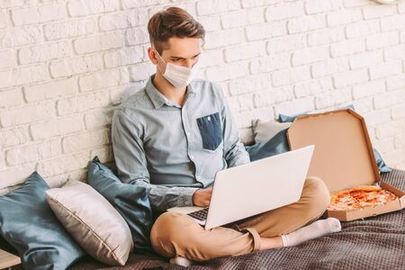 Young businessman in protective mask using laptop for distance job from remote home office. Busy hipster man freelancer in medical face mask surf internet, eat pizza, sit on couch. COVID-19 quarantine