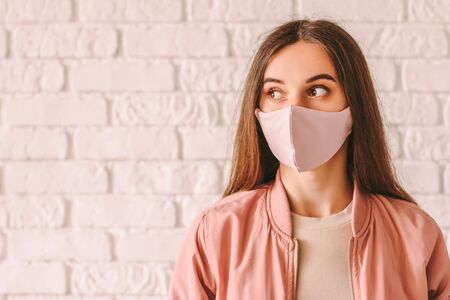 Portrait happy young woman in trendy medical face mask look at copy space. Beautiful stylish hipster girl in pink protective face mask and jacket. Cool fashionable girl. COVID-19 quarantine lifestyle 免版税图像