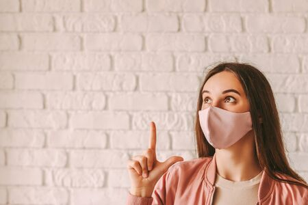 Portrait beautiful trendy hipster woman in pink protective face mask pointing finger at copy space. Young happy girl in stylish medical face mask look at copy space. Coronavirus quarantine lifestyle