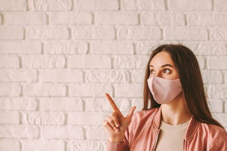 Portrait young beautiful hipster girl in stylish protective face mask look at copy space. Happy trendy woman in pink medical face mask pointing with finger at copy space. COVID-19 quarantine fashion 免版税图像