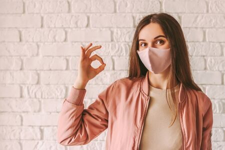 Portrait happy woman in stylish medical face mask showing okay gesture with hand. Beautiful millennial hipster girl in pink protective face mask gesturing ok alright sign. Satisfied girl. Good advice 免版税图像