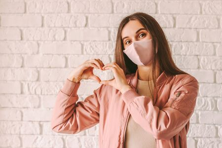 Portrait happy trendy hipster girl in pink medical face mask show heart shape symbol with hands. Young beautiful millennial woman in stylish protective face mask gesturing love peace sign with fingers 免版税图像