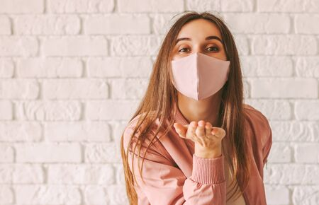Portrait young happy millennial woman in trendy medical face mask blowing air kiss with hand. Beautiful stylish hipster girl in pink protective mask send blow kiss. Girl gesture blow kiss in face mask 免版税图像