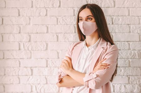 Portrait young confident professional business woman in pink suit and medical face mask with arms crossed. Happy beautiful girl lawyer in stylish protective face mask. Female executive boss smiling