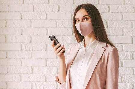 Portrait beautiful happy female entrepreneur in stylish medical face mask and suit using smart phone in office. Young confident business woman in pink protective face mask hold mobile phone in hand