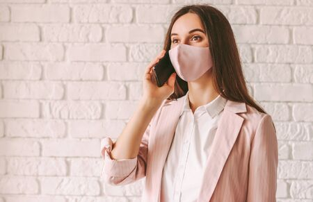 Portrait young happy business woman in pink protective face mask and suit talk mobile phone and smile. Beautiful professional female entrepreneur in stylish pink medical face mask with smart phone