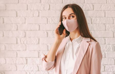 Portrait professional young business woman in stylish suit, medical face mask talk cell phone and smile. Happy beautiful girl entrepreneur in pink protective face mask with smart phone. Communication