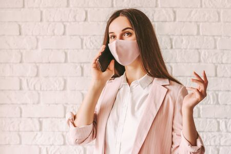Portrait busy young girl entrepreneur in pink medical face mask and suit talk cell phone. Happy beautiful business woman in pink protective face mask have business communication on mobile phone 免版税图像