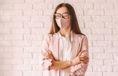 Portrait young professional business woman boss in eyglasses wearing pink medical face mask. Beautiful confident girl entrepreneur in stylish protective face mask, suit and glasses keep arms crossed