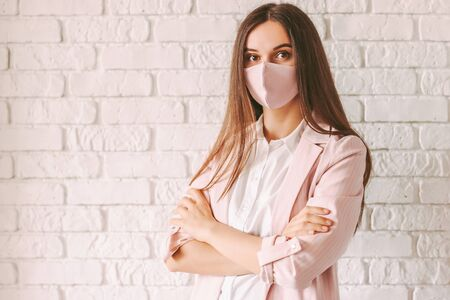 Portrait beautiful young business woman in pink medical face mask and suit with crossed arms in office smiling. Happy confident girl lawyer in pink protective face mask. Female boss, corporate manager
