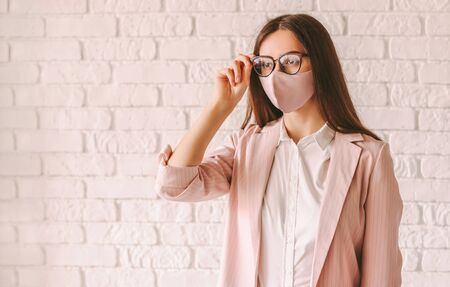 Portrait young confident girl entrepreneur in stylish medical face mask and suit wearing glasses. Beautiful professional business woman in pink protective face mask and eyeglasses. Modern female boss 免版税图像