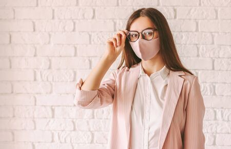 Portrait beautiful professional business woman in pink protective face mask, casual suit and eyeglasses. Young confident female entrepreneur in pink medical face mask wear glasses. Corporate girl boss