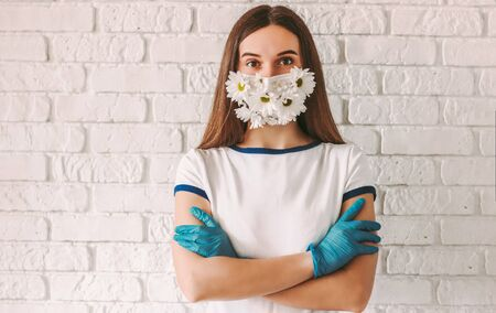 Portrait young confident woman doctor in summer medical face mask keep arms crossed. Happy girl wearing latex medical gloves and protective face mask with flowers. Spring allergy, COVID-19 protection 免版税图像