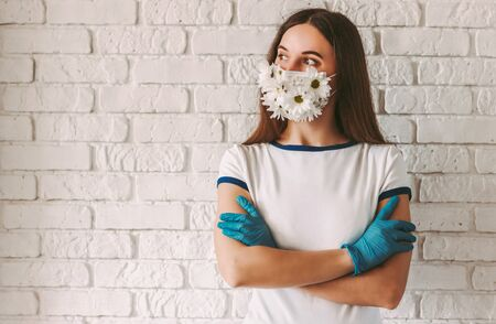 Portrait happy female doctor in summer medical face mask look at copy space and keep arms crossed. Young woman wearing protective face mask and medical gloves for COVID-19 protection. Spring allergy