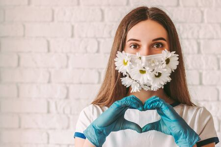 Portrait young happy woman in summer medical face mask and protective gloves show heart shape sign and smiling. Beautiful girl doctor in protective mask with flowers gesture love symbol. Good, charity 免版税图像