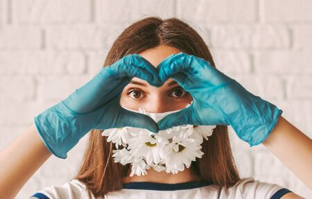 Portrait young woman doctor in medical face mask with flowers and protective gloves show love sign with hands. Happy beautiful girl in summer medical mask gesturing heart shape symbol. Charity, good 免版税图像