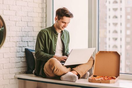 Happy businessman using laptop for distance work from home and eat tasty takeaway pizza fast food. Young hipster man freelancer typing on computer keyboard, study, remote education, sit on windowsill