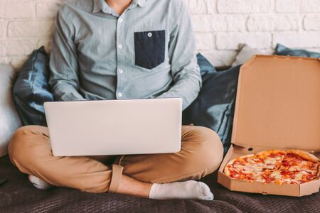 Stylish hipster man student surf internet on laptop and eat pizza at cozy workplace on couch. Busy businessman using computer for remote work at home office. Tasty takeaway fast food for lunch break Imagens