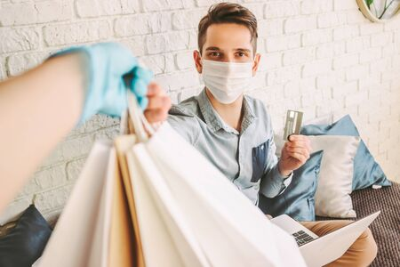 POV of delivery man in protective gloves giving shopping bags and check out customer with credit card. Happy male shopper in medical face mask receiving purchases at home. Safe quarantine delivery