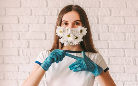 Portrait young girl doctor in medical face mask with flowers remove protective gloves from hands. Happy beautiful woman in protective mask celebrate end of coronavirus COVID-19 fight, take off gloves