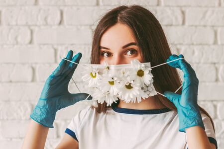 Portrait beautiful young girl in latex protective gloves wearing or take off summer medical face mask. Happy female doctor in medical gloves put on or remove protective mask with flowers. COVID-19 免版税图像
