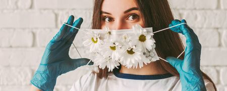 Banner young woman doctor in medical gloves wear or take off protective face mask with flowers. Beautiful happy girl in protective gloves put on or remove summer medical face mask. COVID-19 protection
