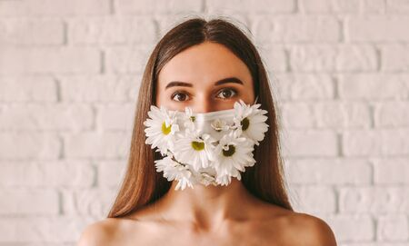 Portrait of young tender woman wearing medical face mask with daisy flowers. Beautiful affectionate girl in summer protective mask. Natural female beauty. Coronavirus COVID-19 quarantine, skin care