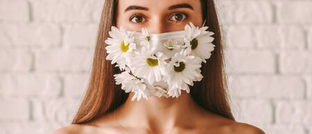 Banner of happy beautiful girl wearing protective mask with spring daisy flowers. Young tender woman in summer medical face mask. Natural female beauty. Skin care, health care. Coronavirus COVID-19 免版税图像