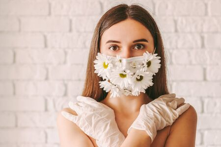 Portrait young tender woman posing in summer medical face mask and latex protective gloves. Happy beautiful girl wearing protective mask with daisy flowers. Natural female beauty. COVID-19 quarantine 免版税图像