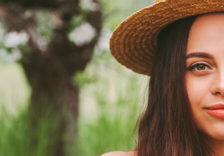 Portrait young beautiful woman in straw hat smiling outdoors. Happy attractive hipster girl posing on blossom countryside garden. Carefree brunette hippie girl in straw hat on sunny green meadow 免版税图像