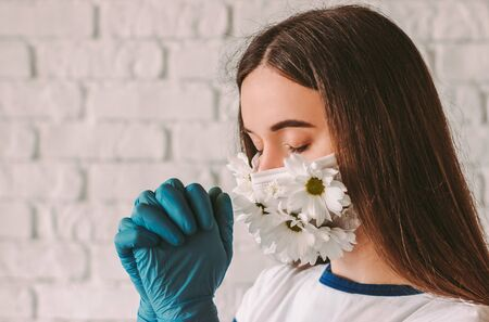 Portrait beautiful religious woman doctor in medical face mask with flowers and protective gloves pray to God for help with coronavirus COVID-19. Young faithful girl in summer face mask. Praying hands 免版税图像
