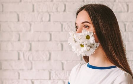 Portrait beautiful young woman doctor in medical face mask with flowers look at copy space, smile. Happy good girl wearing summer protective face mask. Coronavirus COVID-19 protection. Spring allergy