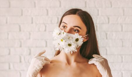 Portrait beautiful tender woman wearing latex protective gloves and medical face mask with daisy flowers. Happy attractive girl fashion model posing in summer protective mask. COVID-19 natural beauty