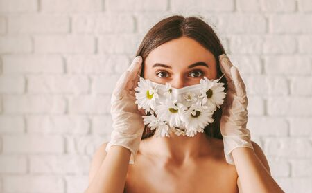 Portrait young beautiful girl fashion model in protective gloves wearing medical face mask with flowers. Attractive tender woman in medical gloves put on summer protective mask. Female natural beauty