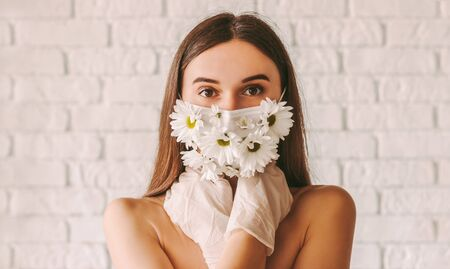 Portrait young affectionate woman posing in protective gloves and summer medical face mask. Beautiful tender girl wearing protective face mask with flowers and latex gloves. Natural female beauty