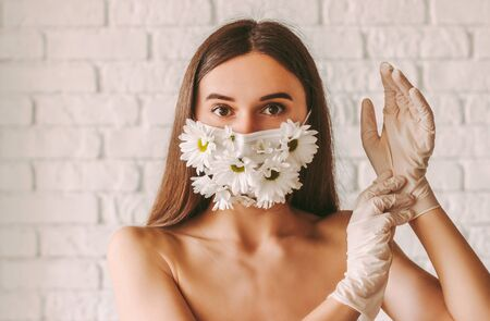 Portrait of young attractive woman wearing latex protective gloves and summer medical face mask. Beautiful tender girl posing in protective face mask with flowers. Female natural beauty. COVID-19 免版税图像