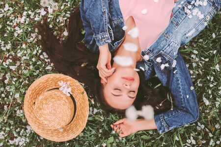 Top view happy beautiful hipster woman relaxing on green grass with blossom flowers. Young carefree hippie girl in stylish denim jacket laying on floral countryside garden. Cute free girl outdoors