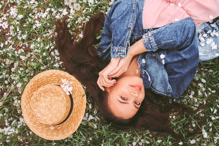 Top view cute happy hipster girl in stylish denim jacket laying on grass on countryside floral garden. Beautiful carefree hippie woman relaxing on summer serene meadow. Woman outdoors, bloom nature