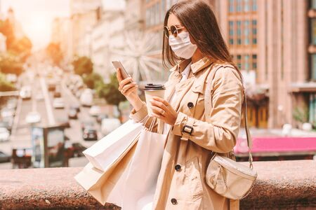 Young stylish hipster woman in medical face mask and sunglasses use smart phone, drink coffee after shopping in mall. Beautiful happy girl in protective face mask with shopping bags on city street 免版税图像