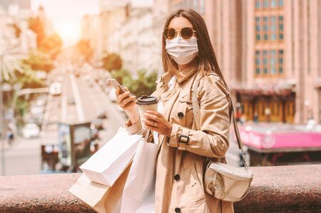 Happy elegant woman in protective face mask with shopping bags on sunny city street. Beautiful stylish hipster girl shopper in medical face mask drink coffee, use mobile phone after shopping in mall