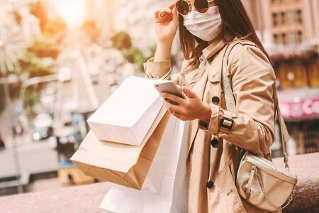 Young happy girl in medical face mask with shopping bags on sunny city street. Stylish elegant woman shopper in protective face mask and sunglasses use mobile phone. Quarantine shopping in city mall
