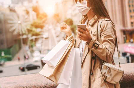 Stylish elegant hipster girl in medical face mask and sunglasses use mobile phone while shopping in city mall. Beautiful young girl shopaholic in protective face mask with shopping bags on city street