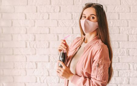 Portrait stylish young woman in pink medical face mask drink cold lemonade. Beautiful trendy hipster girl in stylish protective face mask and pink jacket hold bottle of fresh beverage. Summer fashion 免版税图像