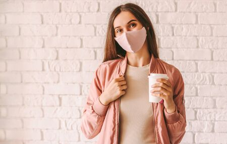 Happy hipster girl in stylish medical face mask and jacket drink coffee from paper cup. Beautiful trendy woman in pink protective face mask hold disposable cup of coffee or tea. Quarantine lifestyle 免版税图像
